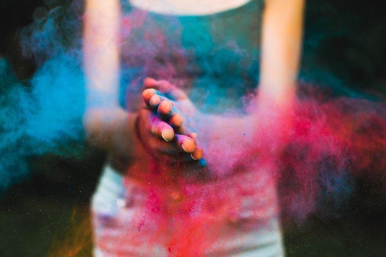 Gehen sie neue Wege in der ganzheitlichen Körperarbeit. Holi, buntes Farbpulver umgeben die Hände einer Frau